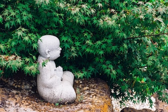 Profile of a small praying Buddha statue under the tree in nature