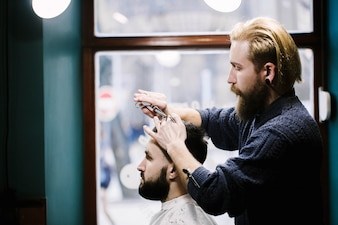 Profile of barber cutting man's hair