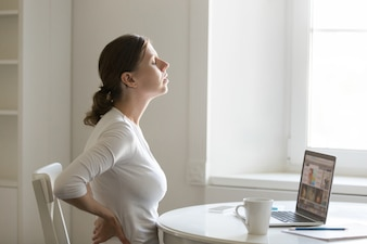 Profile portrait of a woman at desk stretching, backache positio