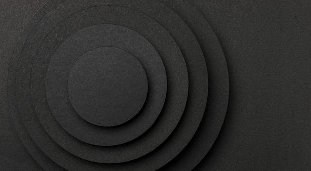 Pyramid of circular pieces of black paper copy space