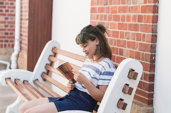 Reading girl sitting on a bench