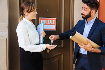 Real estate agent giving key to business woman