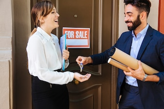 Real estate agent giving key to woman