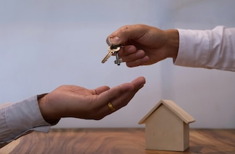 Real estate agent giving keys to customer after contract signature.