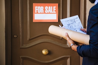 Real estate agent in front of door with for sale sign