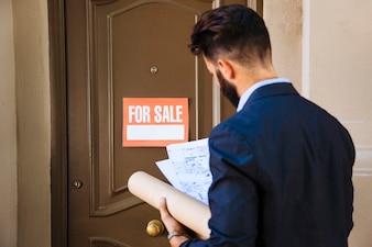 Real estate agent in front of door