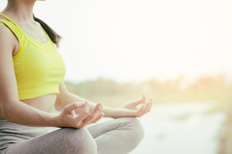 Rear view close up of woman perform meditating yoga on the nature background in the morning.