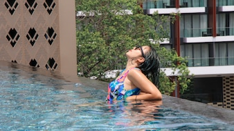 Rear view of a woman swimming at relaxing pool with wide open arms on crystal clear water.