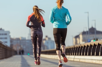 Rear view of active teenagers running
