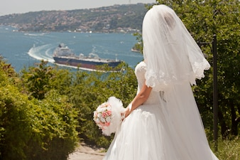 Rear view of bride with bouquet looking at bay