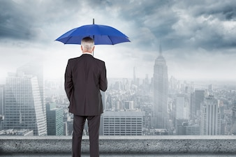 Rear view of businessman with umbrella looking at city
