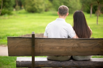 Rear view of couple sitting on a wooden bench outdoors