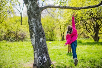 Rear view of girl jumping under a branch