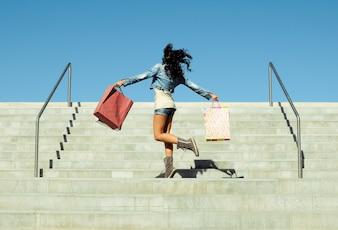 Rear view of girl jumping with shopping bags on the stairs