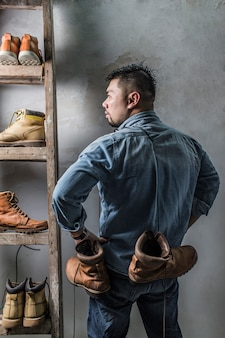 Rear view of shoemaker posing with his boots