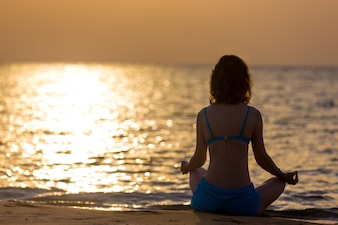 Rear view of woman meditating at sunset