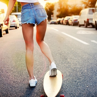 Rear view of young woman in shorts and skateboard