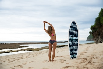 Rear view of young woman warming up before surfing