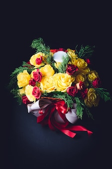 Red and white ribbons twine bouquet of red and yellow roses