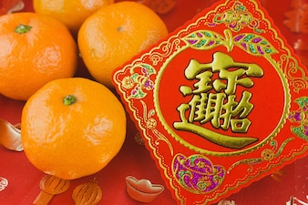 Red card with a tangerine to celebrate the chinese new year