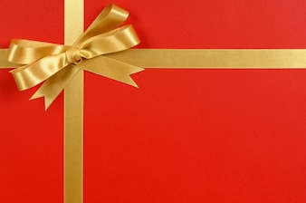 Red christmas gift with a elegant golden bow