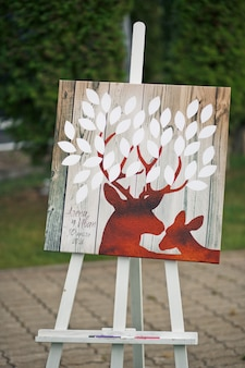 Red deers with white leaves painted on wooden board