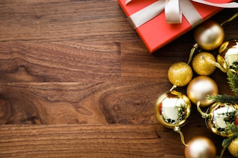 Red gifts and yellow christmas balls on wooden table