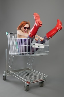 Red girl riding on a shopping cart