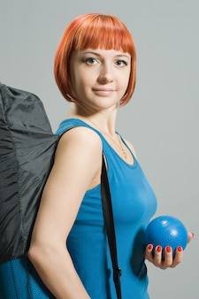 Red-haired fitness girl with yoga mat