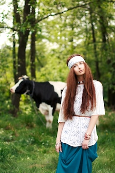 Red-haired woman in the field with a cow behind