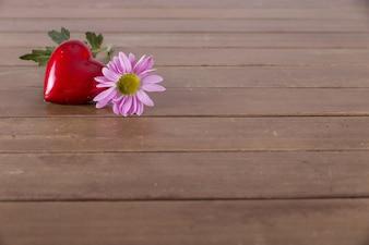 Красное сердце и цветок на столе