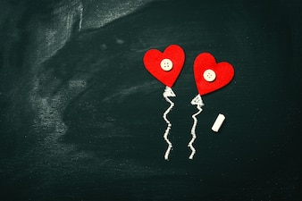 Red hearts on top of a blackboard