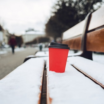Red paper cup stands on snowed bench on alley