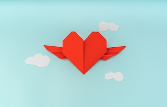 Red paper origami heart with wings and cloud on blue background