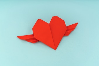 Red paper origami heart with wings on blue background .