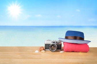 Red pink tower, blue hat, old vintage camera and shells over wooden table on sunshine blue sky and ocean background