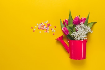Red watering can with flowers on yellow background