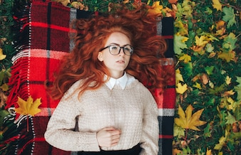 Redhead girl on red plaid in autumn park