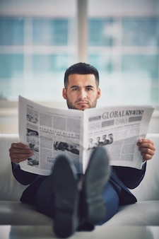 Relaxed businessman reading the newspaper