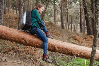 Relaxed girl sitting on a log