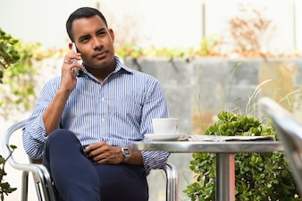 Relaxed Hispanic Man Talking on Phone in Cafe