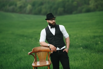 Relaxed man with vest and hat next to a wooden chair