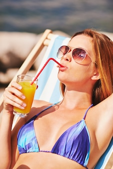 Relaxed woman drinking a juice on the beach