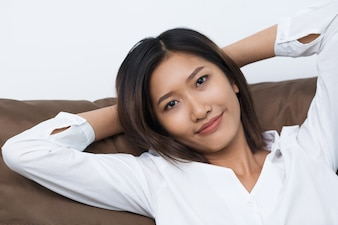 Relaxed Young Asian Woman Lying on Cushion