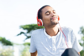 Relaxed young man loving music enjoying nature