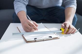 修復、建物と家のコンセプト - クローズアップ男性の手のクリップボードに書く