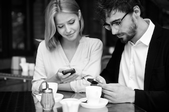 Restful couple connected with smartphone in coffee shop