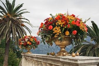 豊富なオレンジと赤の花束は、石の手すりに立つ