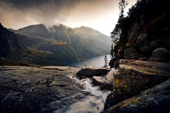 霧の山の風景の中の川。