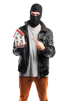 Robber holding a little house